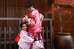 Portrait of a smiling little girl and her mother dressed in bright red and pink kimonos on the street in Gion, Kyoto, Japan