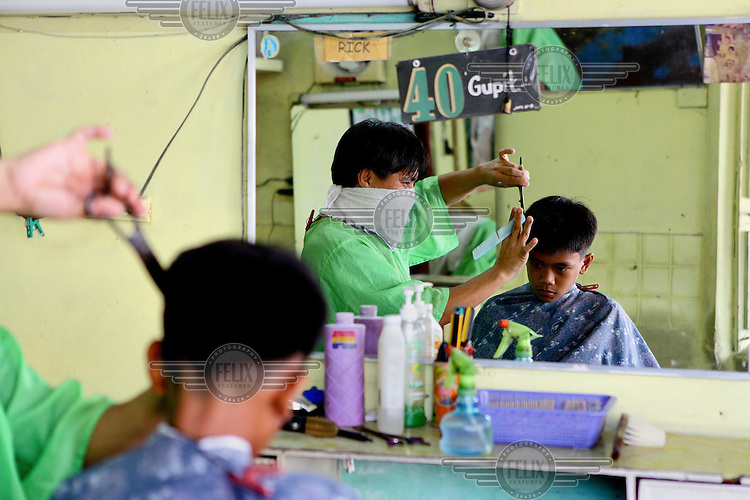 A barber cuts a client's hair, both reflected in a mirror.