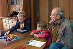 Berkeley CA  Grandpa and grandchildren playing strategy game, Blokus, together  MR
