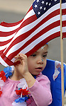 Jocelyn Ortiz, 3, of Vernon, peaks through an flag to see what's happening around her, prior to the step off of the kids parade  in Rockville, Tuesday, July 3, 2012, during Vernon's July 4tn celebration. (Jim Michaud/Journal Inquirer).