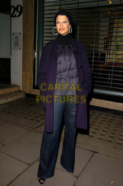 LINDA EVANGELISTA.Stella McCartney Store - Christmas lights switch on, Stella McCartney, London, England. .November 29th, 2007 .full length black coat jacket hands in pocket hat hoop earrings blue grey gray trousers high collar.CAP/CAN.©Can Nguyen/Capital Pictures