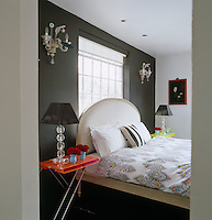 Colourful Lucite bedside tables flank a period French bed against a black wall of the bedroom