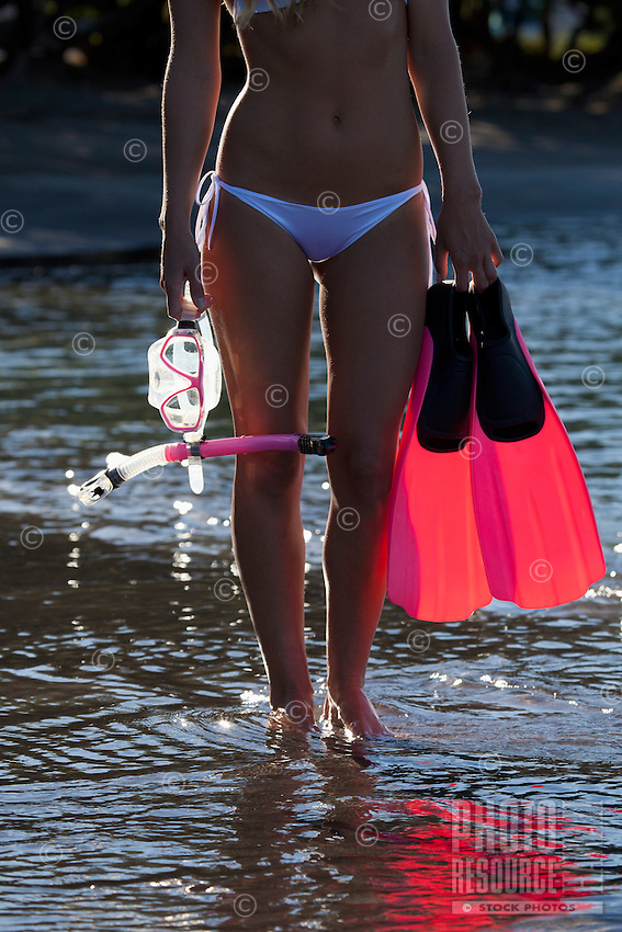 A healthy, fit female heads out to snorkel at Olowalu, Maui.