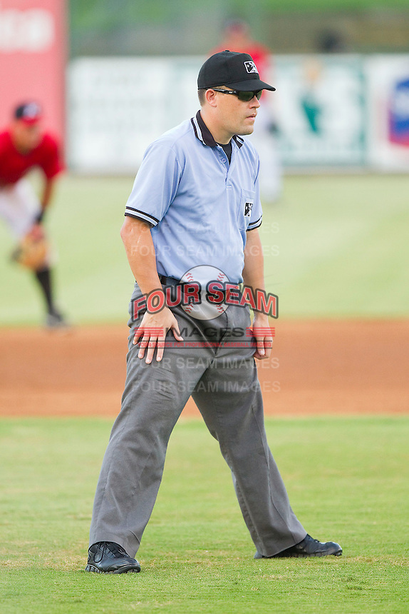 Umpire Cody Oakes handles the calls on the bases during the South Atlantic League game between the Greensboro Grasshoppers and the Kannapolis Intimidators at CMC-Northeast Stadium on July 13, 2013 in Kannapolis, North Carolina.  The Intimidators defeated the Grasshoppers 7-5.   (Brian Westerholt/Four Seam Images)