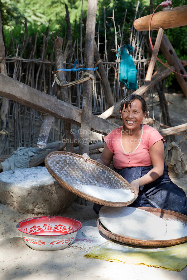 Myanmar, Burma, near Bagan.  Village Woman Sifting Ground Rice.  Her wooden pestle and stone mortar are beside her, on the left.