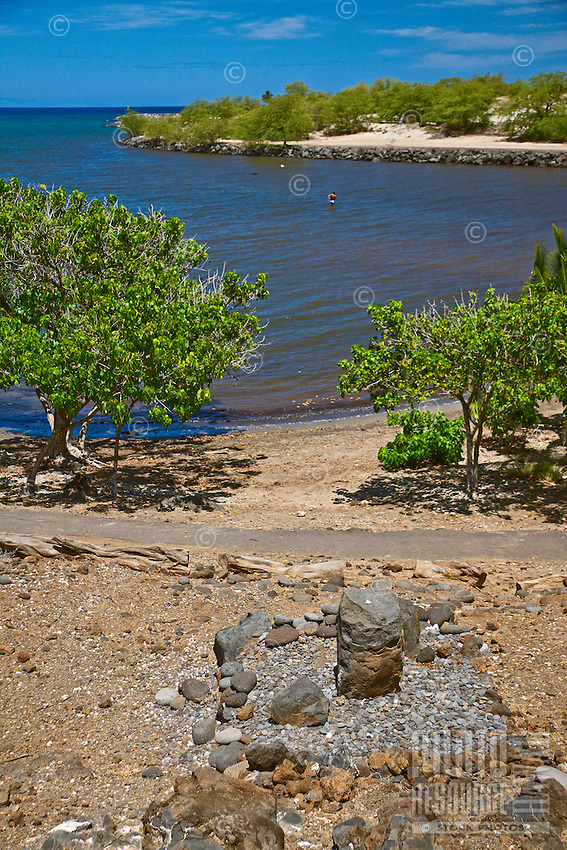 A stone leaning post overlooking the Hale o Kapuni Heiau, or the site of a submerged temple dedicated to the shark gods, Pu'ukohola Heiau National Historic Site, Kawaihae, Kohala, Big Island.