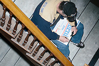 A man writes on a campaign sign while Vermont senator and Democratic presidential candidate Bernie Sanders speaks at a town hall at the Rochester Opera House in Rochester, New Hampshire, on Thurs., Feb. 4, 2016. Press and attendee turnout was low for the event because of scheduling issues. The rally had been scheduled for the previous day, postponed, and then rescheduled just a few hours before the event took place. Later that night, Sanders took part in an MSNBC-sponsored debate with Hillary Rodham Clinton.