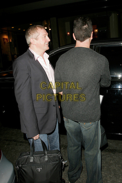 LOUIS WALSH & SIMON COWELL.ITV2 Autumn Launch Party, The Roof Gardens, London, England..August 19th, 2008.full length jeans denim bag grey gray sweater hand profile jacket bag behind rear .CAP/AH.©Adam Houghton/Capital Pictures.