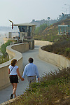 Couple walking along the seawall at Carlsbad State Beach, Carlsbad, San Diego, California