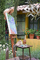 Artist's easel outdoors in the garden with watercolor painting, next to house with shutters, window, flowers, irises aka van Gogh, painting supplies, pot containers, shasta daisies, herbs