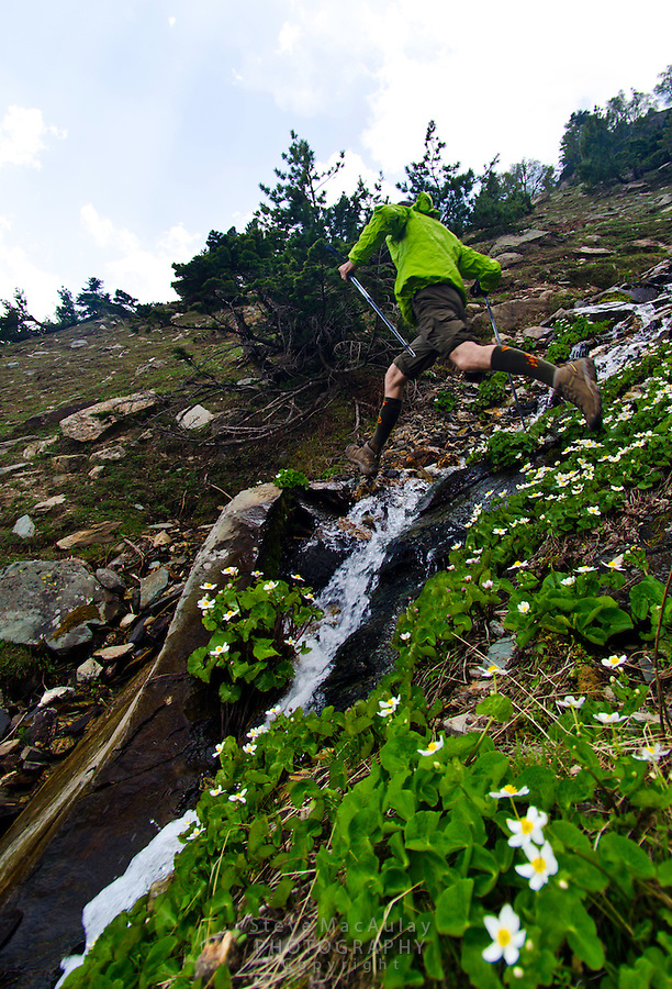 Leaping across a steep creek while trekking in the Himalayan Mountains of Kashmir India.
