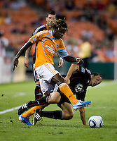 Jed Zayner (12) of DC United tries to take the ball away from Joseph Ngwenya (33) of the Houston Dynamo during their game at RFK Stadium in Washington, DC.  Houston defeated D.C. United, 3-1.