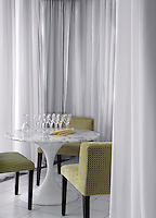 A marble-topped tulip table and striped velvet chairs in the hotel bar are screened by sheer white curtains