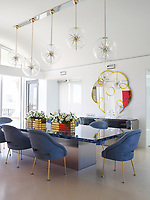 The luxurious penthouse apartment is full of edgy chic and retro styling. The dining room chairs include two originals by Maison Leleu, from Maison Gerard, as well as reproductions, all covered in a nubuck from Cortina Leathers; the resin-top table is a custom design, and five Italian pendants form a single light fixture.