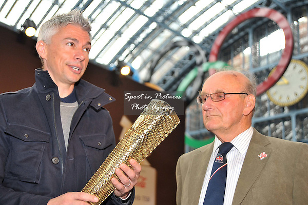 Jonathan Edwards holds the torch as Austin Playfoot (Torchbearer at the London 1948 Olympics) looks on. 2012 London Olympic Torch Prototype designed by Edward Barber and Jay Osgerby. St Pancras Station. London. 08/06/2011. MANDATORY Credit Sportinpictures/Garry Bowden - NO UNAUTHORISED USE - 07837 394578