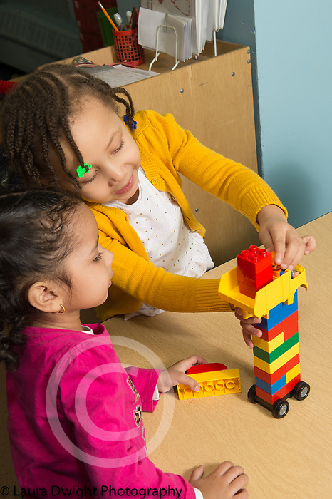 Education Preschool 3 year olds two girls playing together with Duplo colorful plastic building blocks