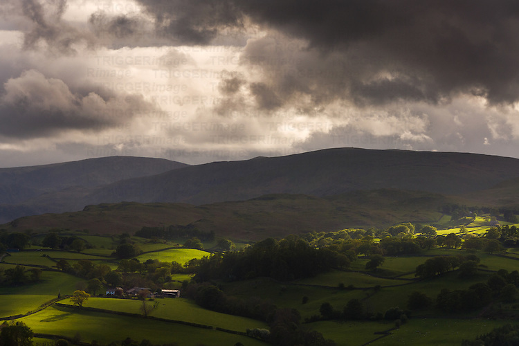 Patches of sunlight on green fields and moorland