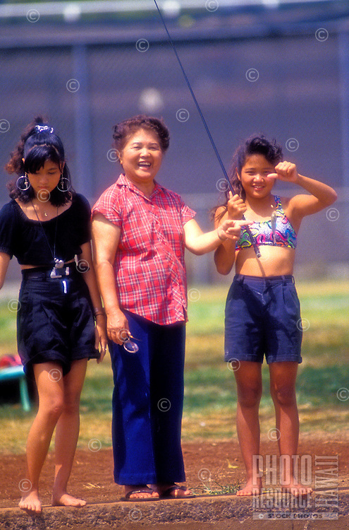 Grandmother and two granddaughters fishing together near a stream on Oahu, Hawaii