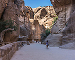 Tourists hike into a narrow slot canyon called the Siq to see the ruins of the Nabataean city of Petra in the Hashemite Kingdom of Jordan.  Petra Archeological Park is a Jordanian National Park and a UNESCO World Heritage Site.