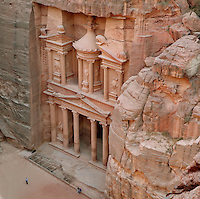 Treasury of the Pharaohs or Khazneh Firaoun, 100 BC - 200 AD, Petra, Ma'an, Jordan. Originally built as a royal tomb, the treasury is so called after a belief that pirates hid their treasure in an urn held here. Carved into the rock face opposite the end of the Siq, the 40m high treasury has a Hellenistic facade with three bare inner rooms. Petra was the capital and royal city of the Nabateans, Arabic desert nomads. People on the plaza give an idea of the scale of the edifice. Picture by Manuel Cohen