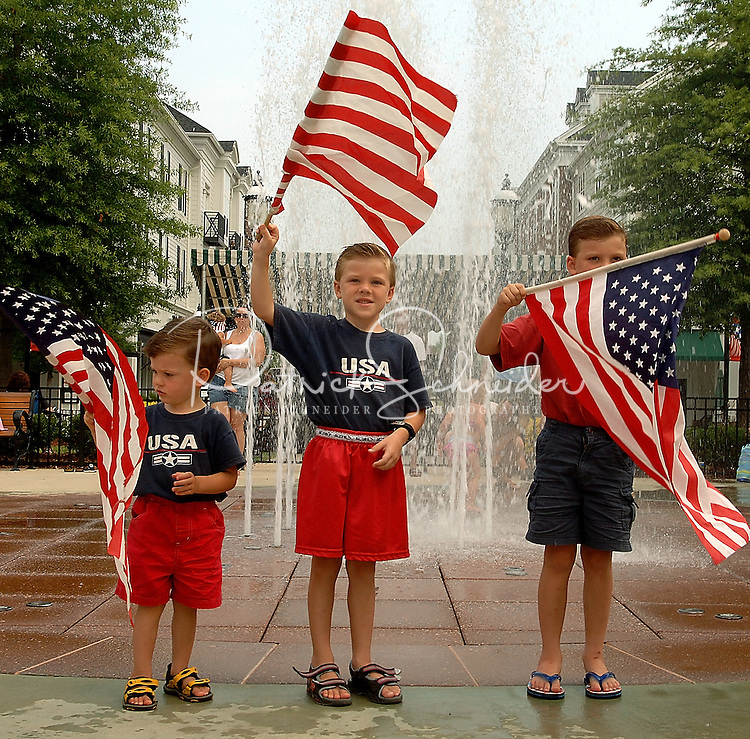 Three boys wave flags during the annual Fourth of July Celebration and community parade in Birkdale Village in Huntersville, NC. Birkdale Village combines the best of shopping, dining, apartments and entertainment venues within a 52-acre mixed-use development.