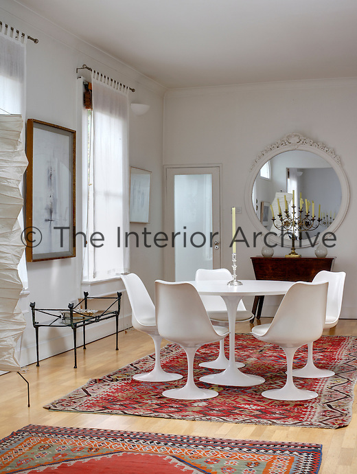 In the dining room the stark white Saarinen Tulip table and chairs have been placed on an elaborately patterned kilim to stunning effect