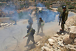 Israeli soldiers move to reestablish a road block moments after using a concussion grenade to disperse protesters during a demonstration against Israel's controversial separation barrier in the West Bank town of Beit Jala near Bethlehem on 04/07/2010.
