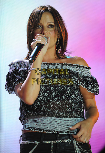SARA EVANS.2008 CMA Music Festival Nightly Concert held on Vault Concert Stage at LP Field, Nashville, Tennessee, USA..June 8th, 2008.stage concert live gig music performance half length black white pattern off the shoulder top microphone singing .CAP/ADM/LF.©Laura Farr/AdMedia/Capital Pictures.