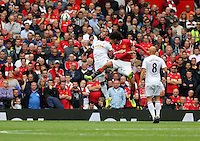 Pictured L-R: Ashley Williams of Swansea batlles for a header against Marouane Fellaini of Manchester United. Saturday 16 August 2014<br />