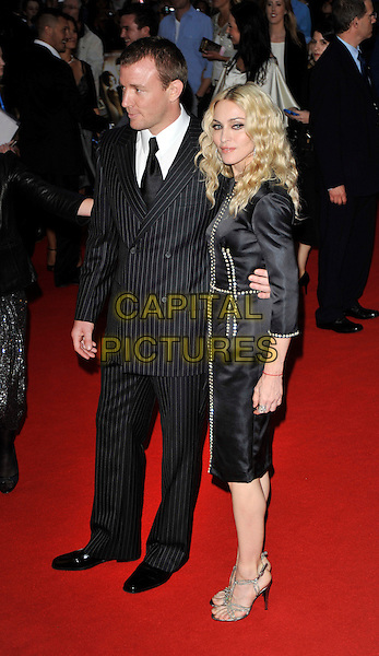 "GUY RITCHIE & MADONNA.Arrivals for the ""RocknRolla"" world film premiere held at the Odeon West End cinema, Leicester Square, London, England..September 1st, 2008.full length black suit tie pinstripe Stella McCartney dress silver shoes sandals red kabbalah bracelet jewel encrusted married couple husband wife grey gray .CAP/CAN.©Can Nguyen/Capital Pictures."