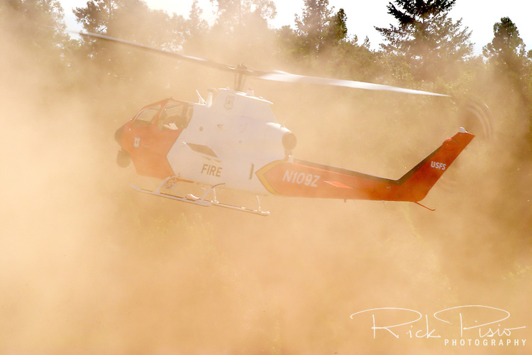"A United States Forest Service 'Firewatch' Helicopter dusts off from the Grass Valley Air Attack Base in California's Sierra Nevada mountains to fight a forest fire. The USFS ""Firewatch"" helicopter is based on a demilitirized Army Cobra gunship with the chin gun removed and replaced with a forward looking infrared thermal imaging system that allows the crew to send images to the command center to show where a forest fire's hot spots are. In addition the thermal imaging system the aircraft is also equipped with a Traffic Collision and Avoidance System for identifying other aircraft in the vicinity, an onboard computer, geo-locating capabilities to aid in low visibility and microwave for sending live infrared videos back to fire camp at a distance of up to 30 miles. Photographed 07/05"