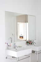 A mirror above two white bathroom sinks with chrome tap fittings
