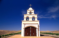 USA, California, Paso Robles, Spanish Mission style church on hill with grape vineyard