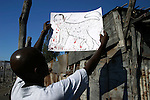 February 16, 2004. Gonaives, Haiti. The People for the Liberation of Haiti in Gonaives march for freedom. Rebels hold this northern city of Gonaives after Anti-Aristide  forces drove away the police and mayor. A caricature of President Aristide is being held up in front of Butteur base camp.