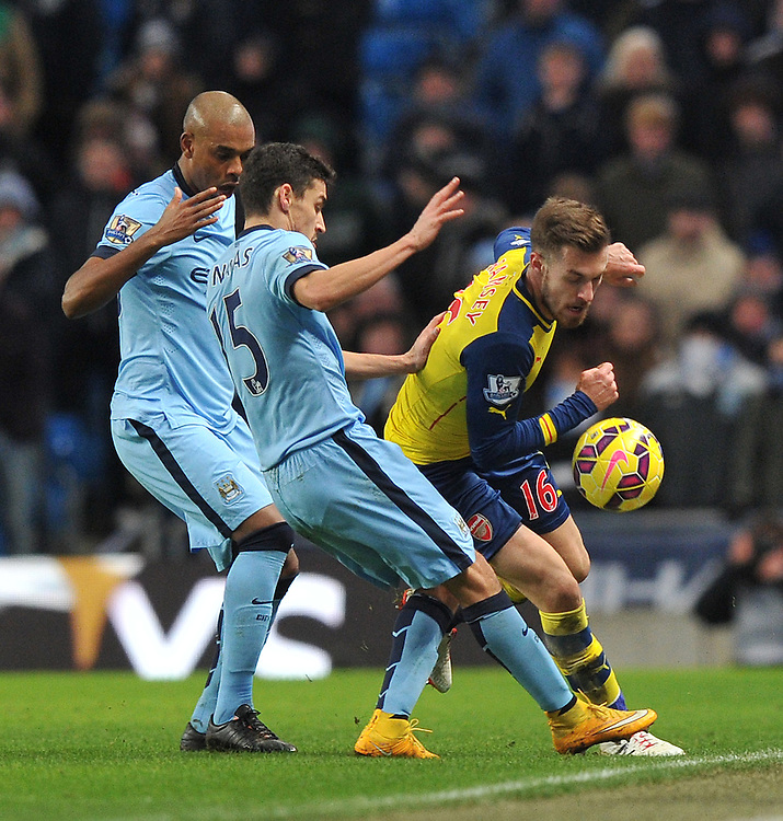 Arsenal's Aaron Ramsey battles with Manchester City's Jes&uacute;s Navas and Fernando<br /> <br /> Photographer Dave Howarth/CameraSport<br /> <br /> Football - Barclays Premiership - Manchester City v Arsenal - Sunday 18th January 2015 - Etihad stadium - Manchester<br /> <br /> &copy; CameraSport - 43 Linden Ave. Countesthorpe. Leicester. England. LE8 5PG - Tel: +44 (0) 116 277 4147 - admin@camerasport.com - www.camerasport.com