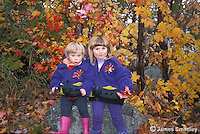 Little girls with matching sweaters sitting on a rock near some trees in fall