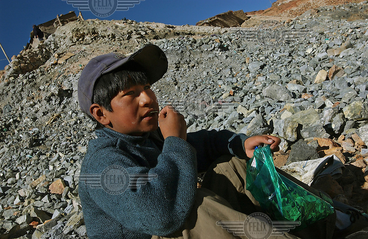 12 year old Jose Lucas Benabides chews coca leaves among the tailings in the compound of a silver mine, where he works with his mother.  The leaves stave off hunger and thirst, allowing him to work throughout the day without pausing for a lunch break.  His late father was a miner who died 5 years ago of silicosis, a respiratory disease caused by the inhalation of silica dust.  Widows of miners are permitted to scour the discarded rocks in search of silver ore to sell....Photo: Dermot Tatlow/Panos Pictures/Felix Features