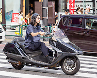A motorcyclist. Men with long hair are quite rare in Tokyo. Even rock and metal fans usually cut their hair short, unless they work in music or bar industries.