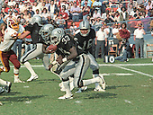 Los Angeles Raiders quarterback Jim Plunkett (16) has handed the ball to running back Marcus Allen (32), who is carrying the ball as fullback Kenny King (33) looks for somebody to block during the game against the Washington Redskins at RFK Stadium in Washington, D.C. on October 2, 1983.  The Redskins won the game 37 - 35.<br /> Credit: Howard L. Sachs / CNP
