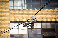 Sneakers suspended form overhead lines on Bogart Avenue in the Bushwick neighborhood of Brooklyn in New York on Saturday, April 27, 2013. The neighborhood is undergoing gentrification changing from a rough and tumble mix of Hispanic and industrial to a haven for hipsters, forcing many of the long-time residents out because of rising rents.. (©Richard B. Levine)