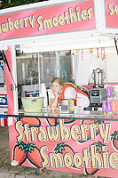 A worker waits for customers in a smoothie stand at the Iowa State Fair in Des, Moines, Iowa, on Sun., Aug. 11, 2019.