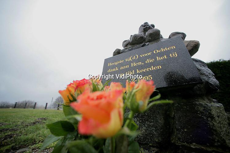 Foto: VidiPhoto..OCHTEN - Onbekenden hebben maandag bloemen geplaatst bij het dijkmonument in Ochten. De sculptuur herinnert aan de vele vrijwilligers die tien jaar geleden bij Ochten door het plaatsen van zandzakken een dijkdoorbraak wisten te voorkomen. Exact een decennium geleden moesten zo'n 200.000 inwoners van het Rivierengebied evacueren als gevolg van het hoge water en de grote kans op een dijkdoorbraak.