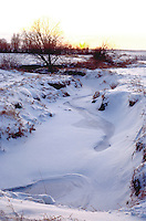 Sunset on a frozen creek on the Iowa plains.  Garden City Iowa USA