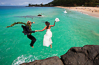 "A couple in wedding attire jumping off the Waimea ""jump rock"" on the North Shore of O'ahu."