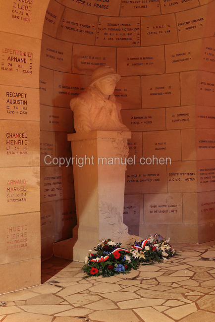 Statue of soldier with floral tributes in the cloister of the Ossuaire de Douaumont or Douaumont Ossuary, designed by Leon Azema, Max Edrei and Jacques Hardy, inaugurated 7th August 1932 by French President Albert Lebrun, to house the remains of French and German soldiers who died at the Battle of Verdun in World War One, at Douaumont, Verdun, Meuse, Lorraine, France. The ossuary contains the remains of over 130,000 soldiers, some of whom are named on the plaques covering the walls and ceiling. The adjoining military cemetery holds 16,142 graves and is the largest single French military cemetery of the First World War, inaugurated in 1923 by Verdun veteran Andre Maginot. It has been listed as a national cemetery. Picture by Manuel Cohen