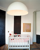 In the baby's bedroom the large circular ceiling light hanging above the cot is made of fibreglass and the pastel drawing on the wall is a work by Etienne de Bary