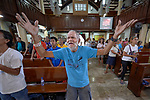 William Pardinio raises his arms during worship at Knox United Methodist Church in Manila, Philippines. The service is part of a weekday program where the church opens up to poor people in the neighborhood, offering showers, food, fellowship, and an opportunity to worship together.