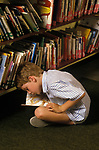 Short sighted child trying to read primary school reading books England London. 1980s.