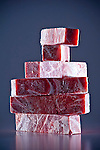 Uniform cuts of frozen meat laying on dark background