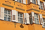 Bright mustard yellow building and shuddered windows in historical old town of Bolzano, Italy